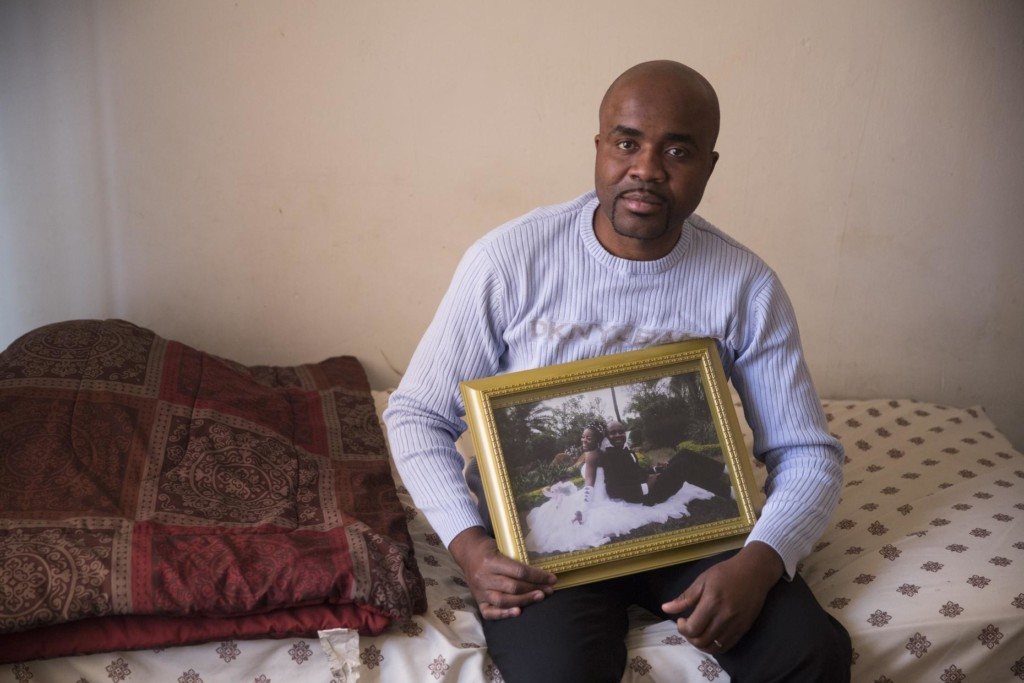Andre Twendele in his apartment in Elizabeth, N.J., holding a photo from his wedding.