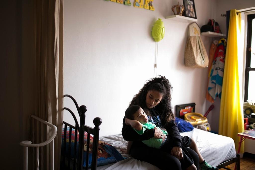 Sakia Colon holds her son, Carter Nunez, in their apartment.